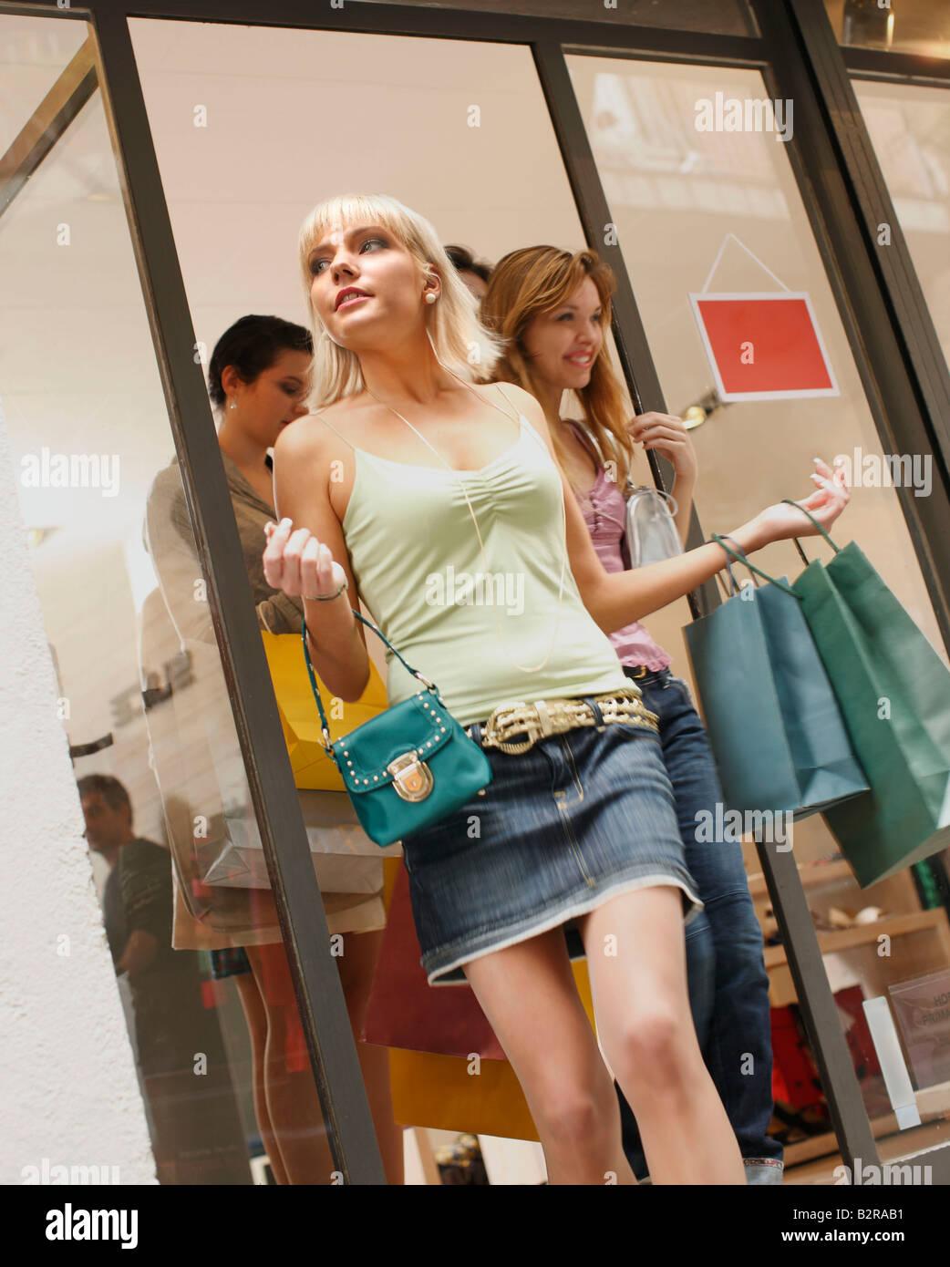 Les jeunes femmes sortant de shop vente Photo Stock