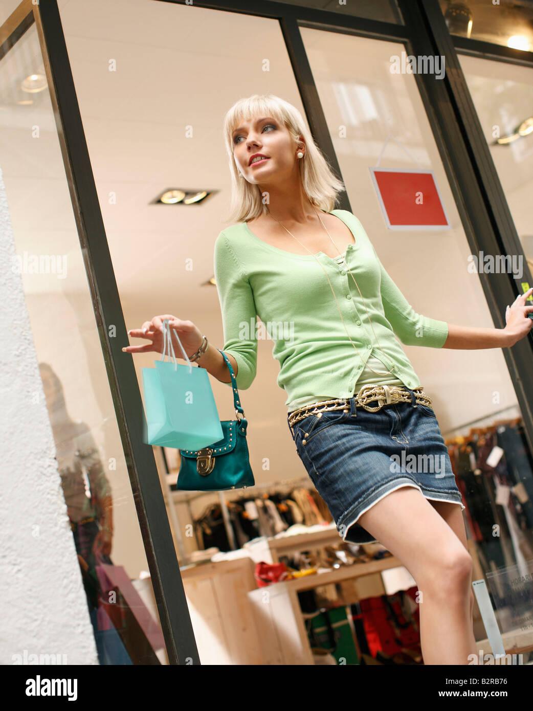 Jeune femme sortant de shop vente Photo Stock