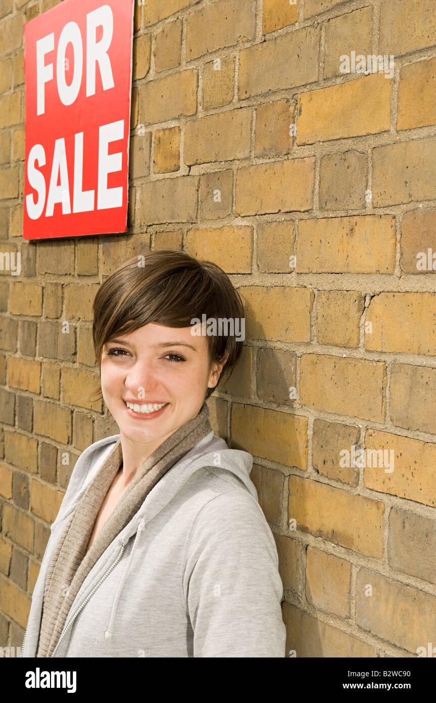 Jeune femme et for sale sign Photo Stock