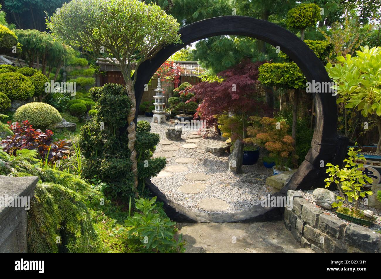 Jardin de style japonais avec moon gate rocks arbustes et arbres ...