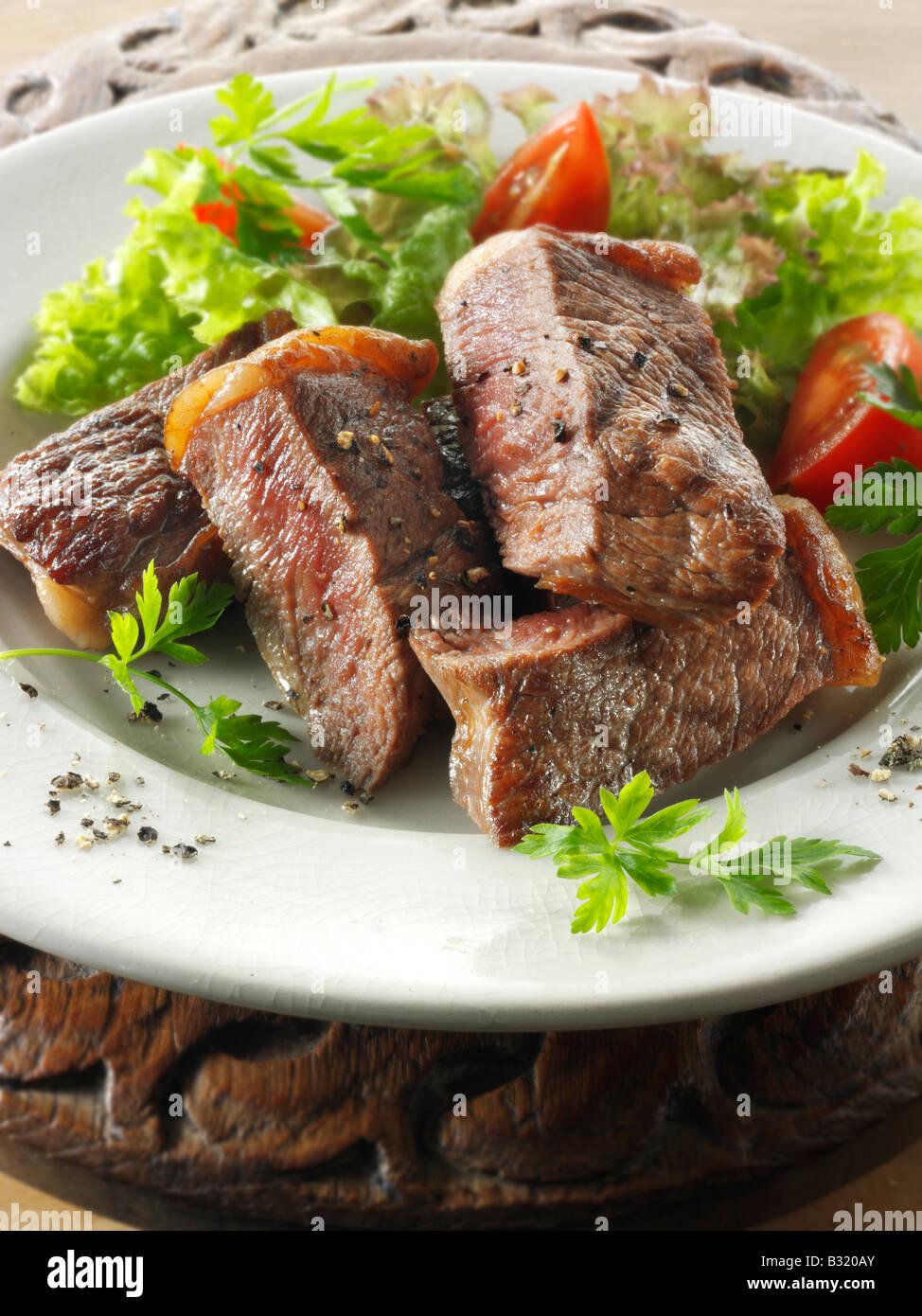 Steak de faux filet de boeuf frais et salade mixte Photo Stock