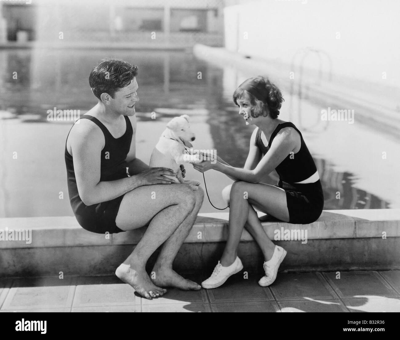 Couple assis avec leur chiot à côté d'une piscine Photo Stock