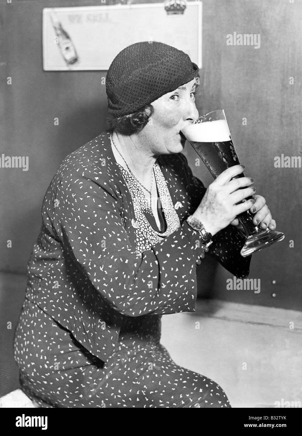 Femme buvant hors d'un grand verre de bière Photo Stock