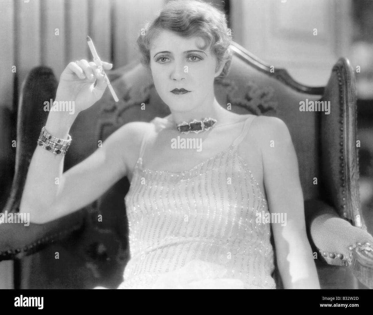 Femme élégante dans une robe de soirée et bijoux fumer une cigarette ... c9b4e51c948c