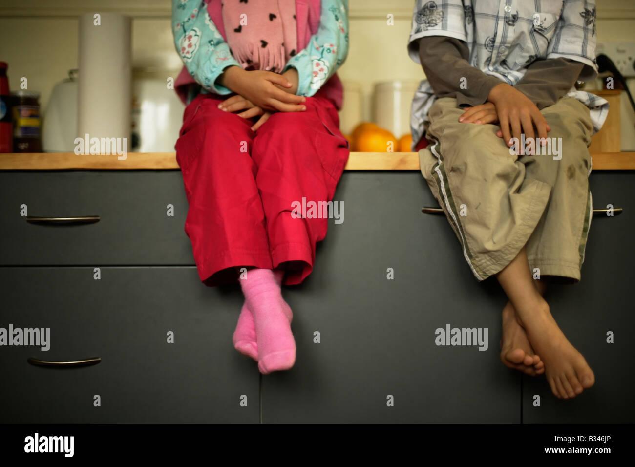 Assis sur le plan de travail de cuisine fille âgée de cinq et six frère regarder la préparation Photo Stock