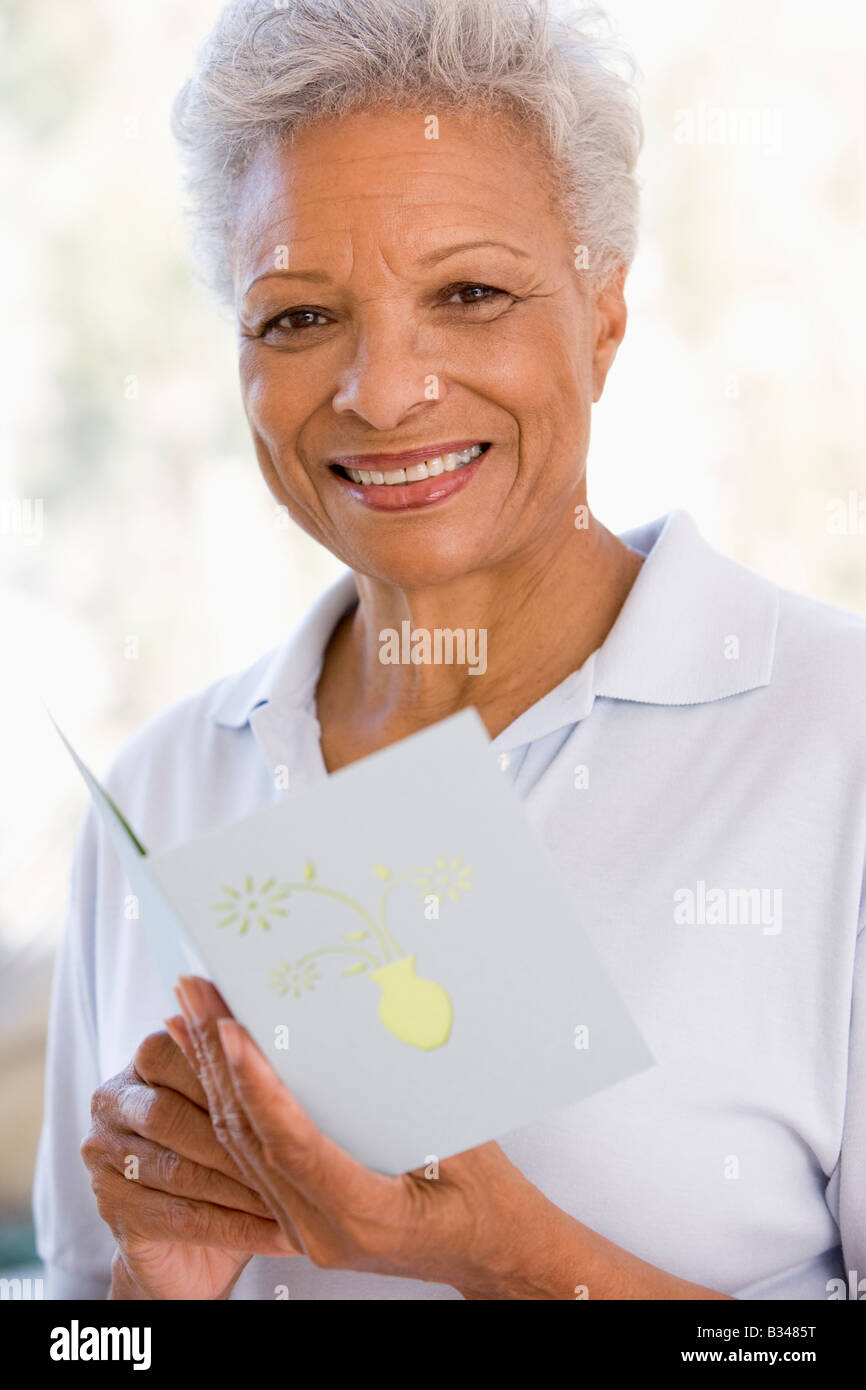 Femme de la lecture de la carte et souriant Photo Stock