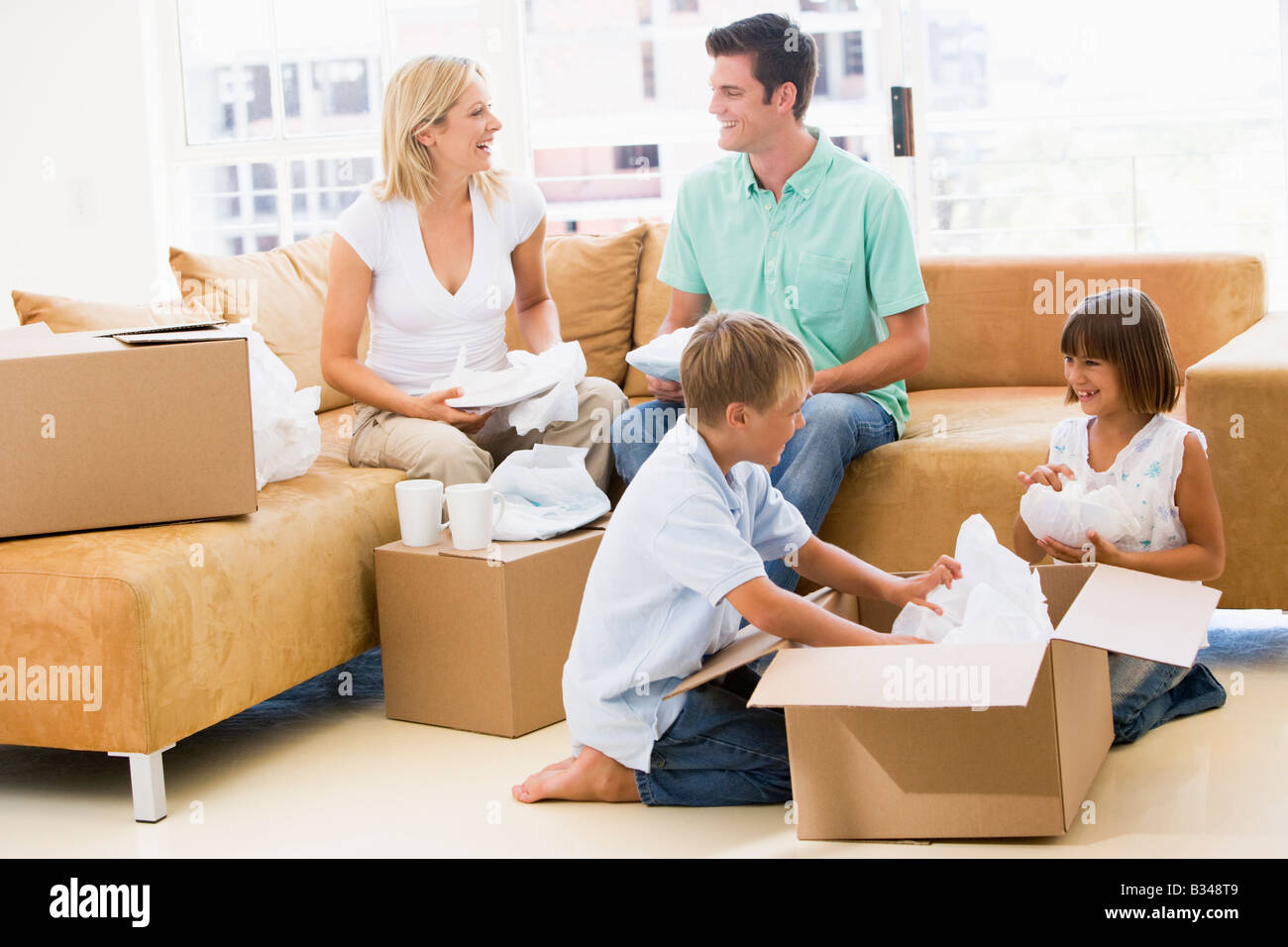 Family unpacking boxes in new home smiling Photo Stock