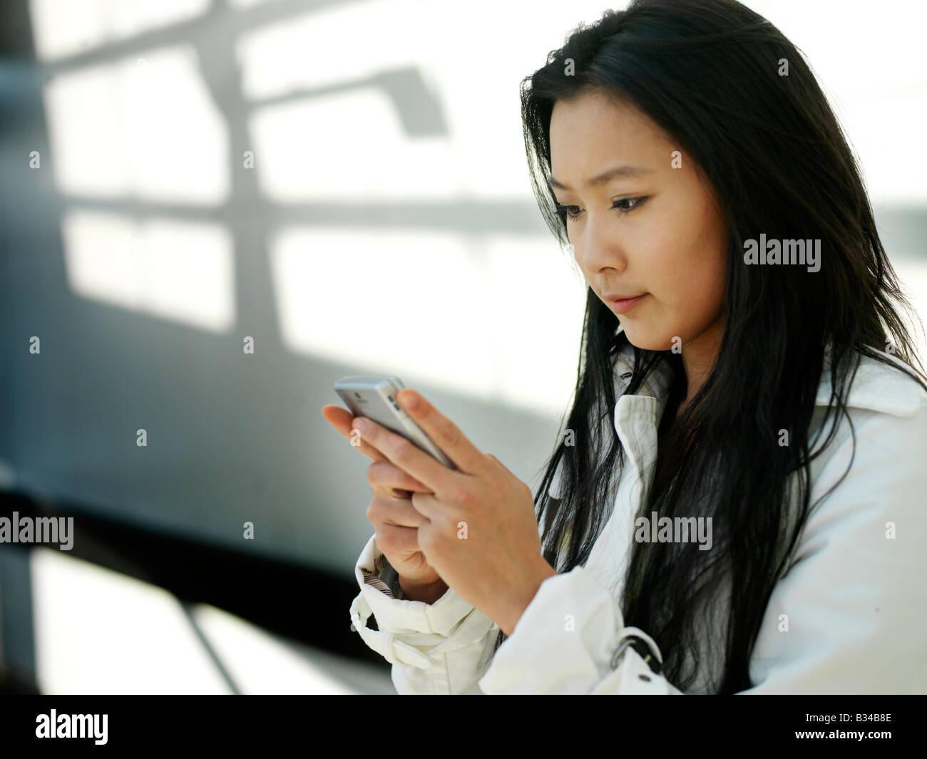Une jeune femme d'affaires chinois en utilisant son téléphone mobile PDA dans la ville. Banque D'Images