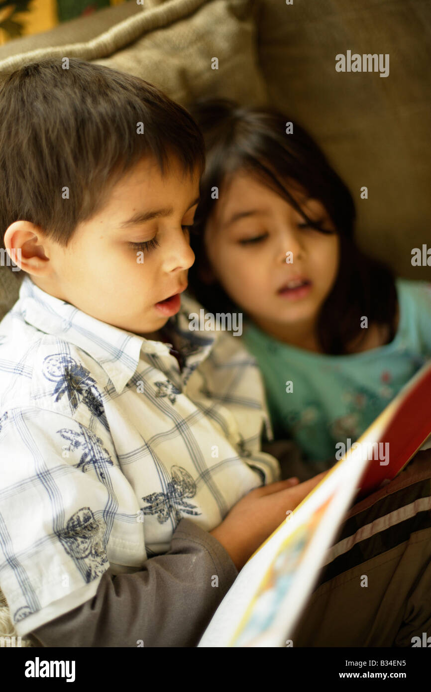 Garçon de 6 ans lit une histoire à sa petite sœur de 5 ans Photo Stock