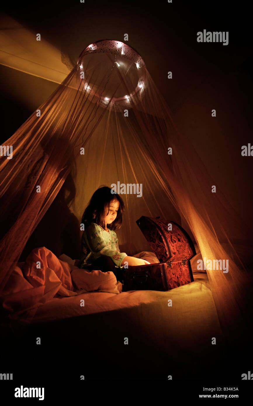 Le coffre au trésor magique fille de cinq ans s'assoit sur le lit à baldaquin et ouvre une boîte Photo Stock