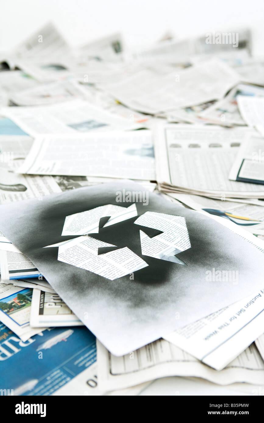 Symbole de recyclage inscrit sur pile de journaux Photo Stock
