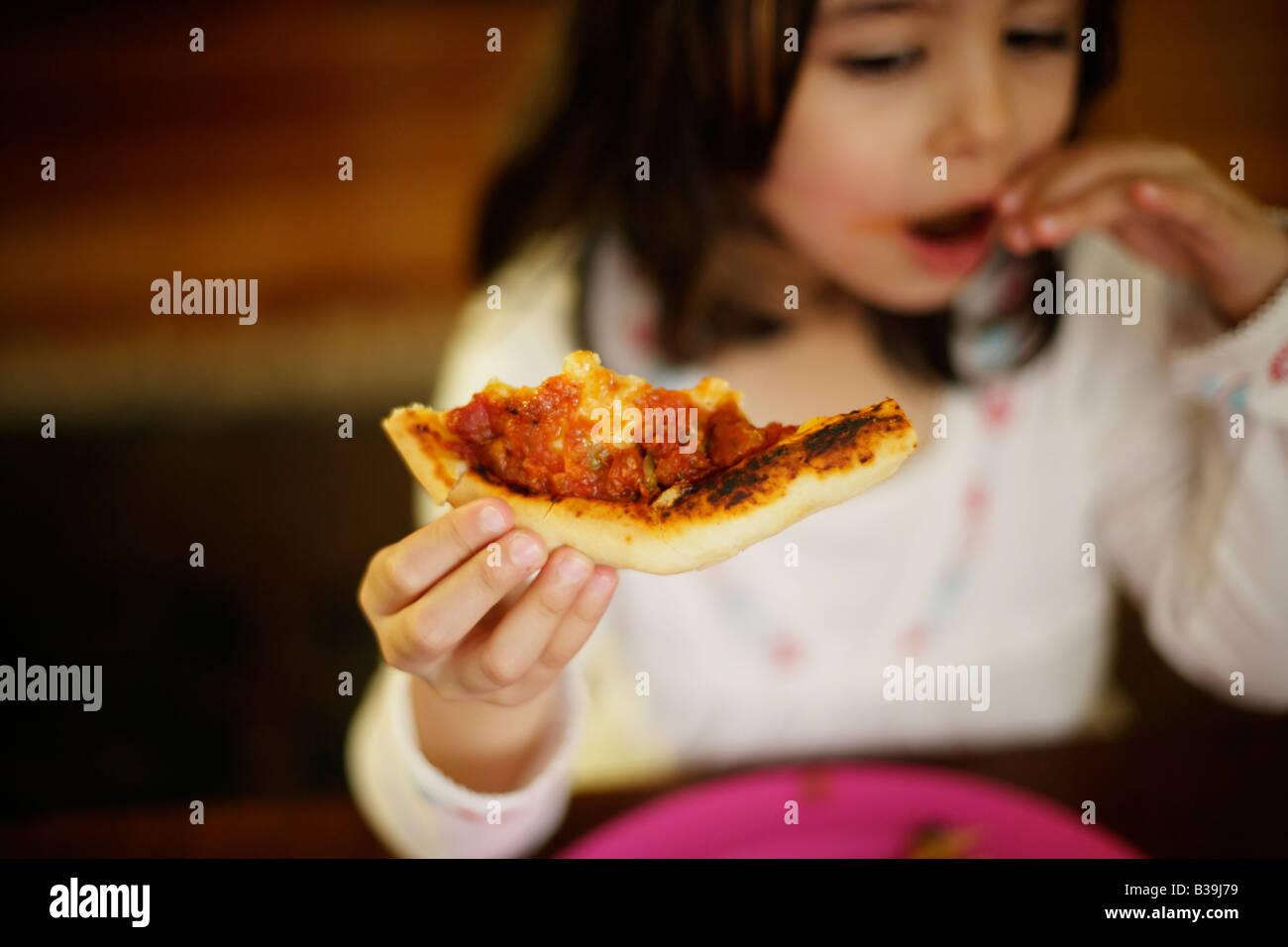 Des pizzas fille de cinq ans prend bouchée de pizza bien chaude du four frais Photo Stock