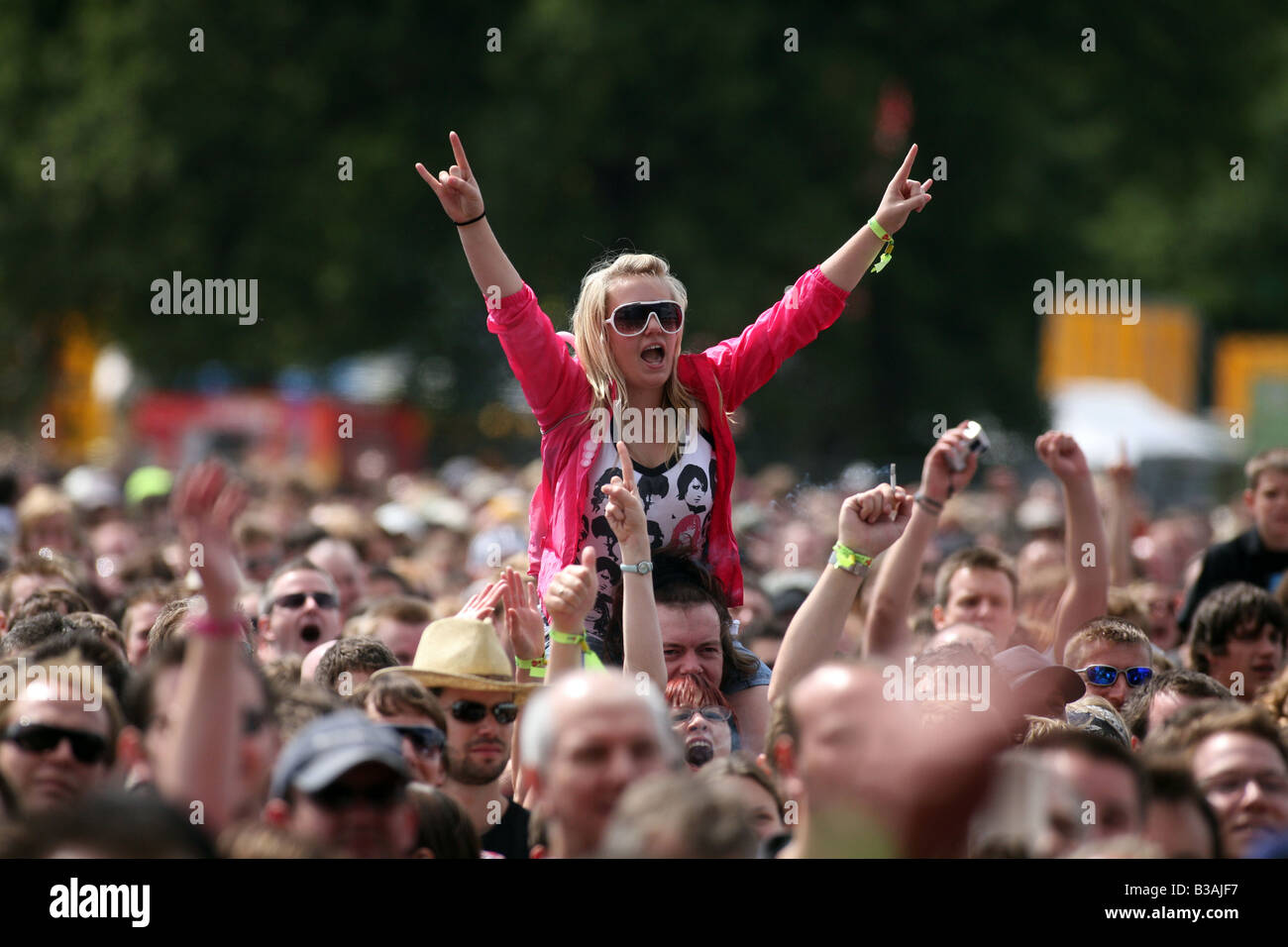 Une fille dans la foule appréciant la musique du V Festival à Hylands Park, Chelmsford Essex Banque D'Images