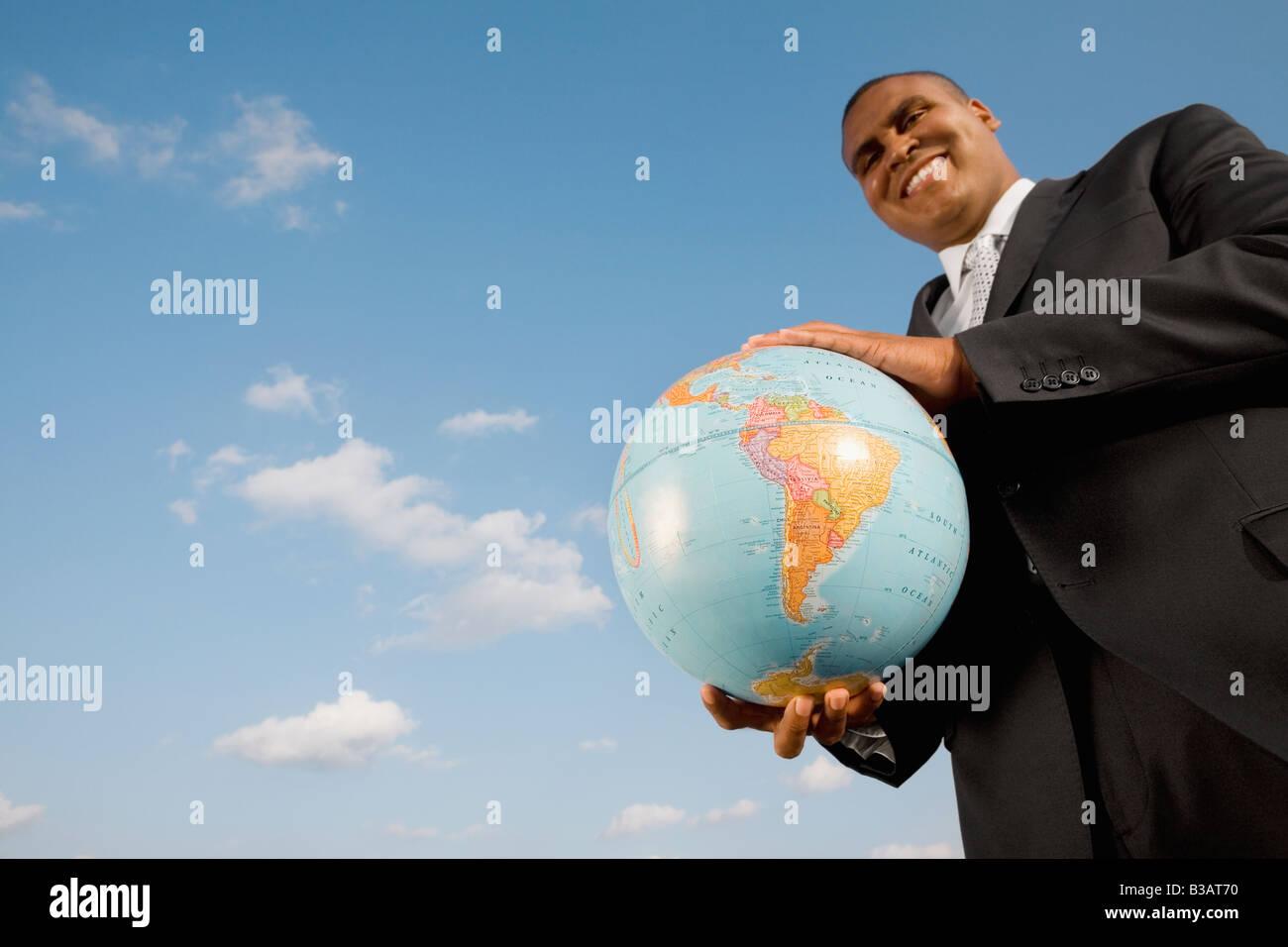 African businessman holding globe Banque D'Images