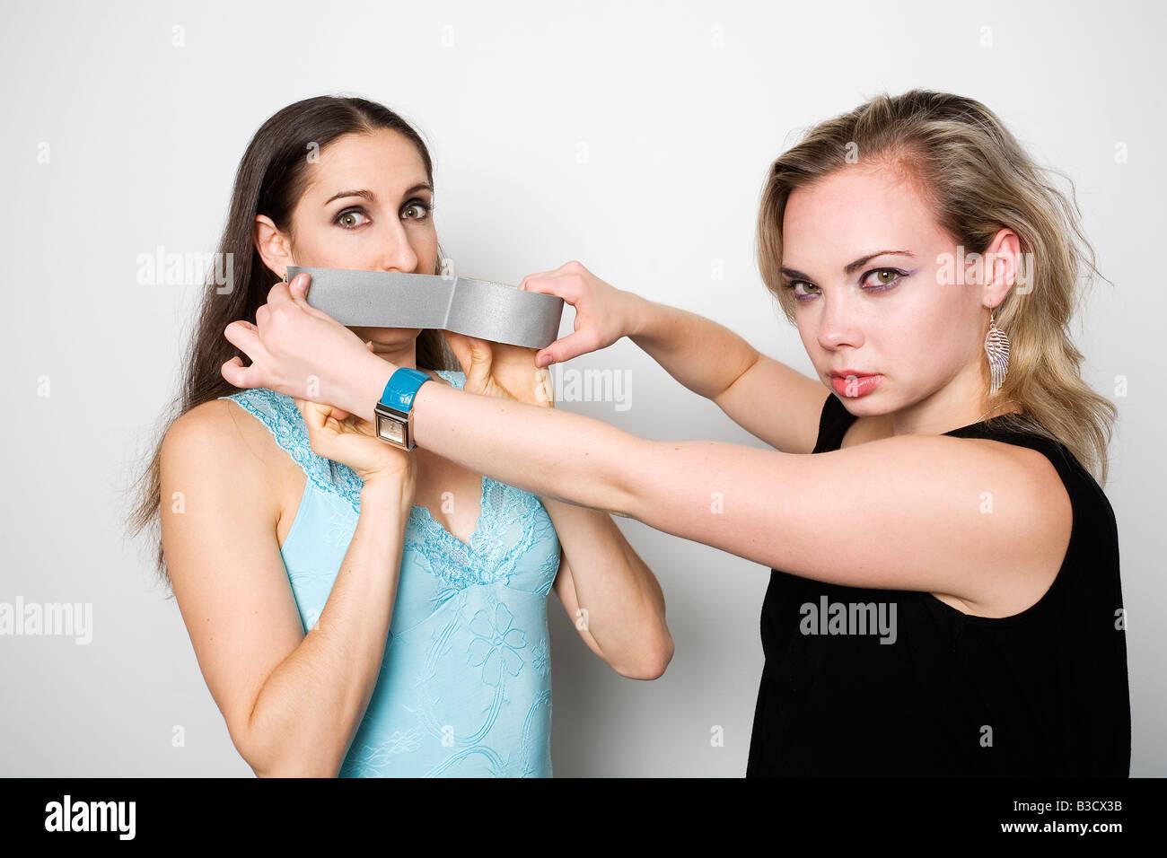 Jeune femme tenant un ruban adhésif sur la bouche d'un ami Banque D'Images