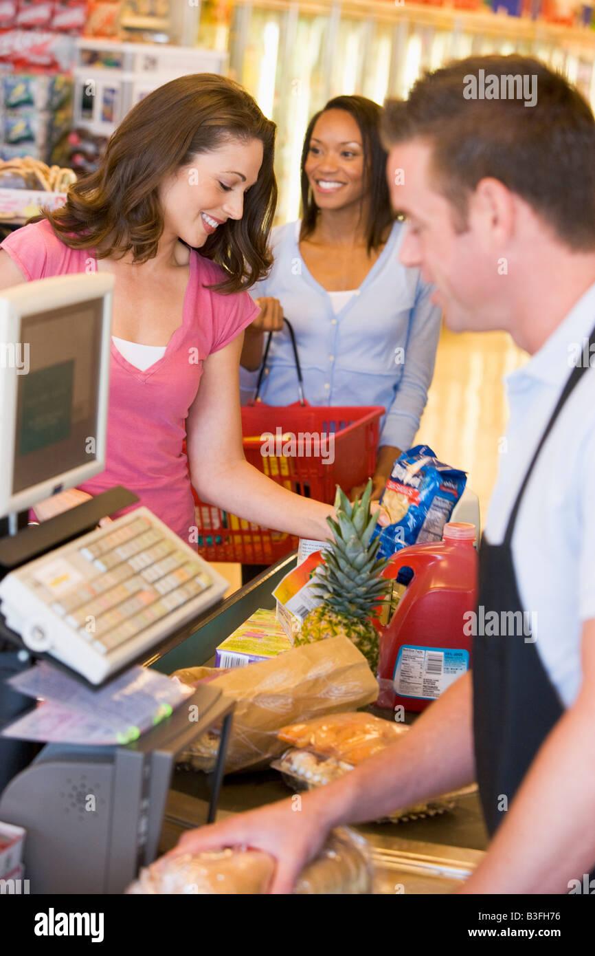 Femmes payant pour les achats à l'épicerie Photo Stock