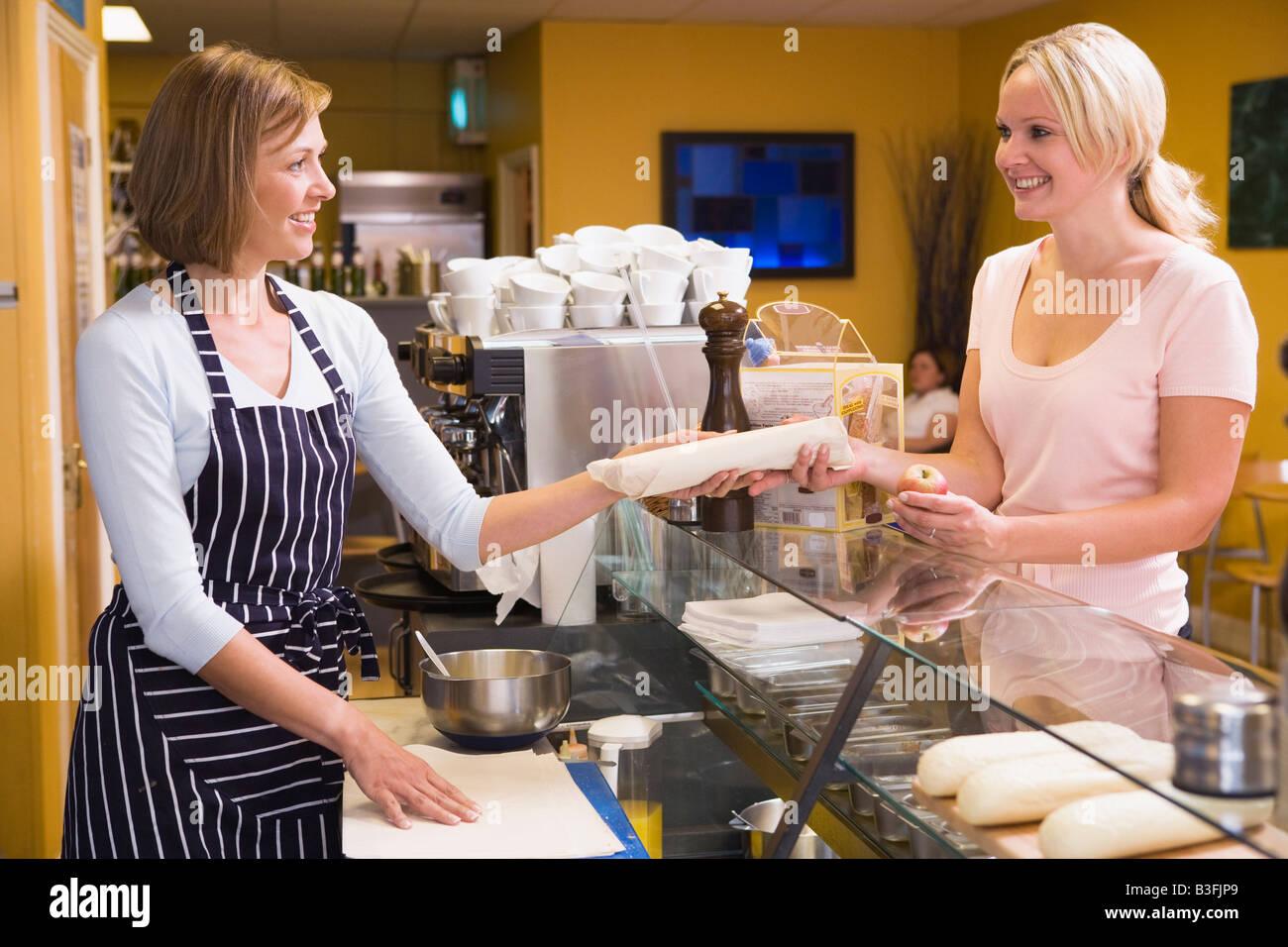 Femme debout au comptoir dans restaurant servant de client Photo Stock