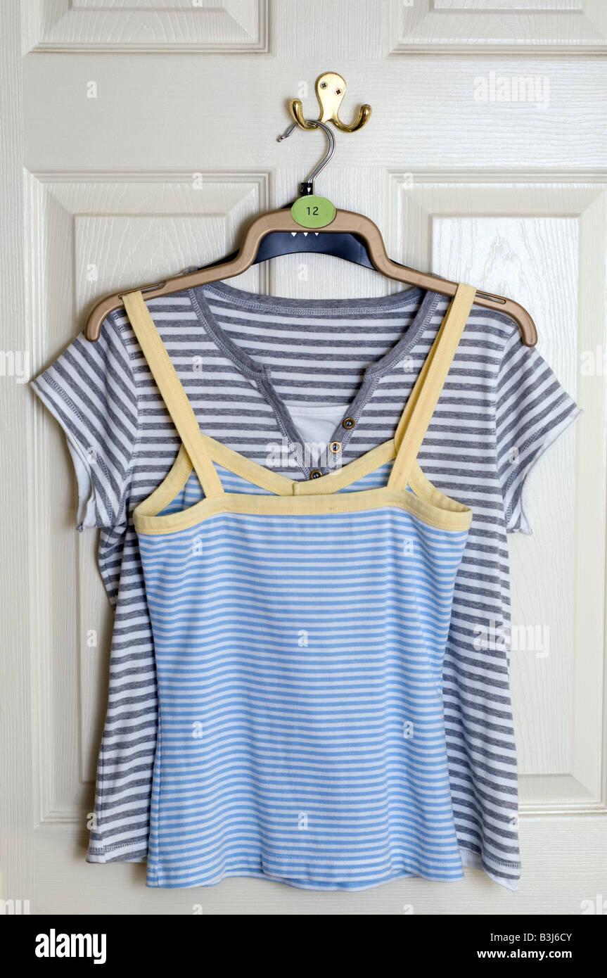 Deux dames taille 12 t shirts d'été suspendu à un crochet à l'arrière d'une porte blanche Banque D'Images