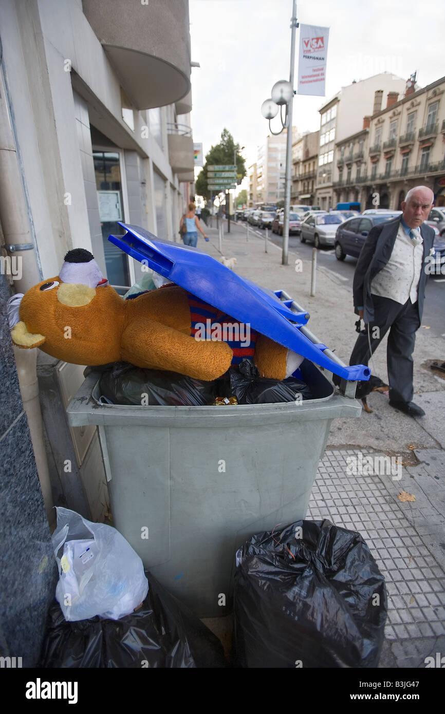 Un homme et chien marche passé un bac portant un ours à Perpignan France Photo Stock