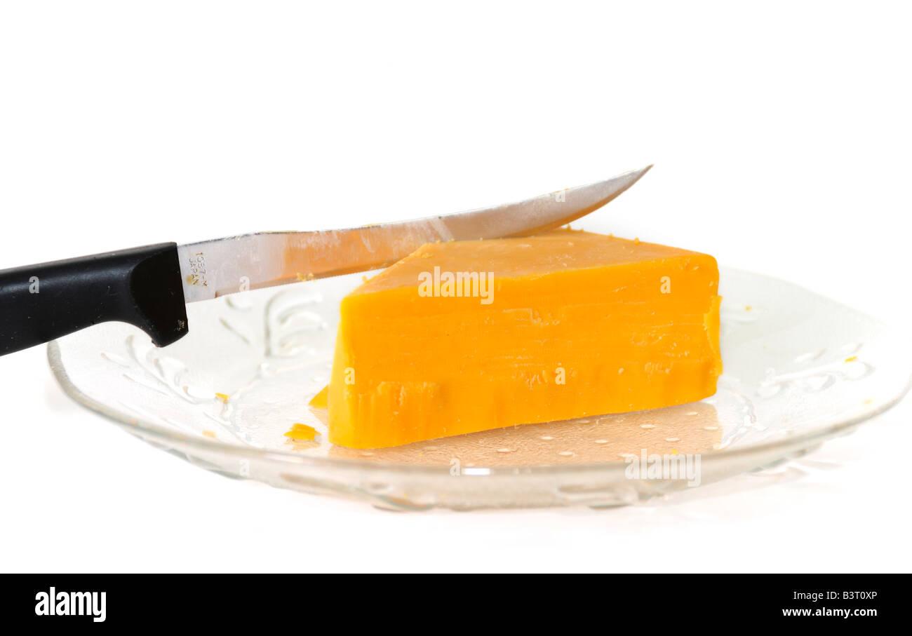 Un morceau en forme de triangle de fromage cheddar avec couteau sur une petite plaque de verre taillé sur fond blanc. Banque D'Images
