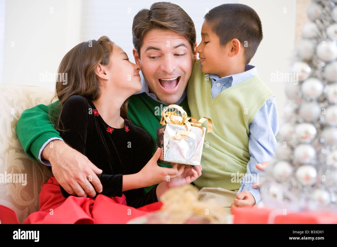 Père Étant donné un cadeau de Noël par sa fille et fils Banque D'Images