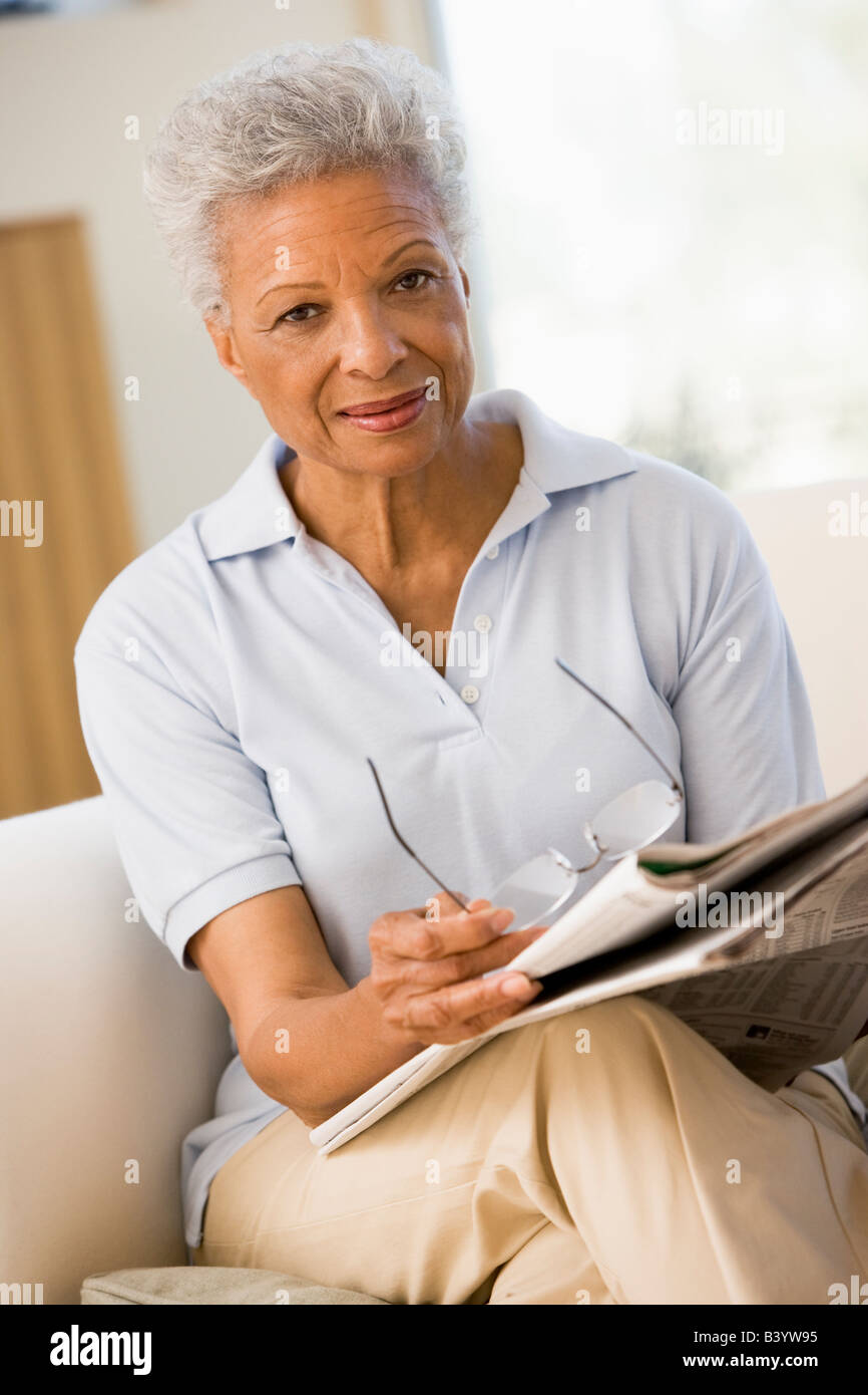 Femme avec un journal holding eyeglasses Banque D'Images
