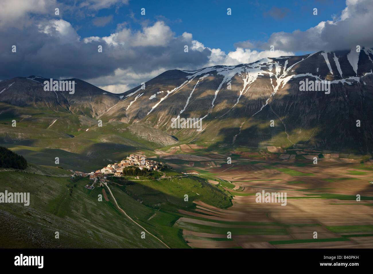 Le village de Castelluccio perché au-dessus du Piano Grande avec les montagnes du parc national Monti Sibillini, Photo Stock