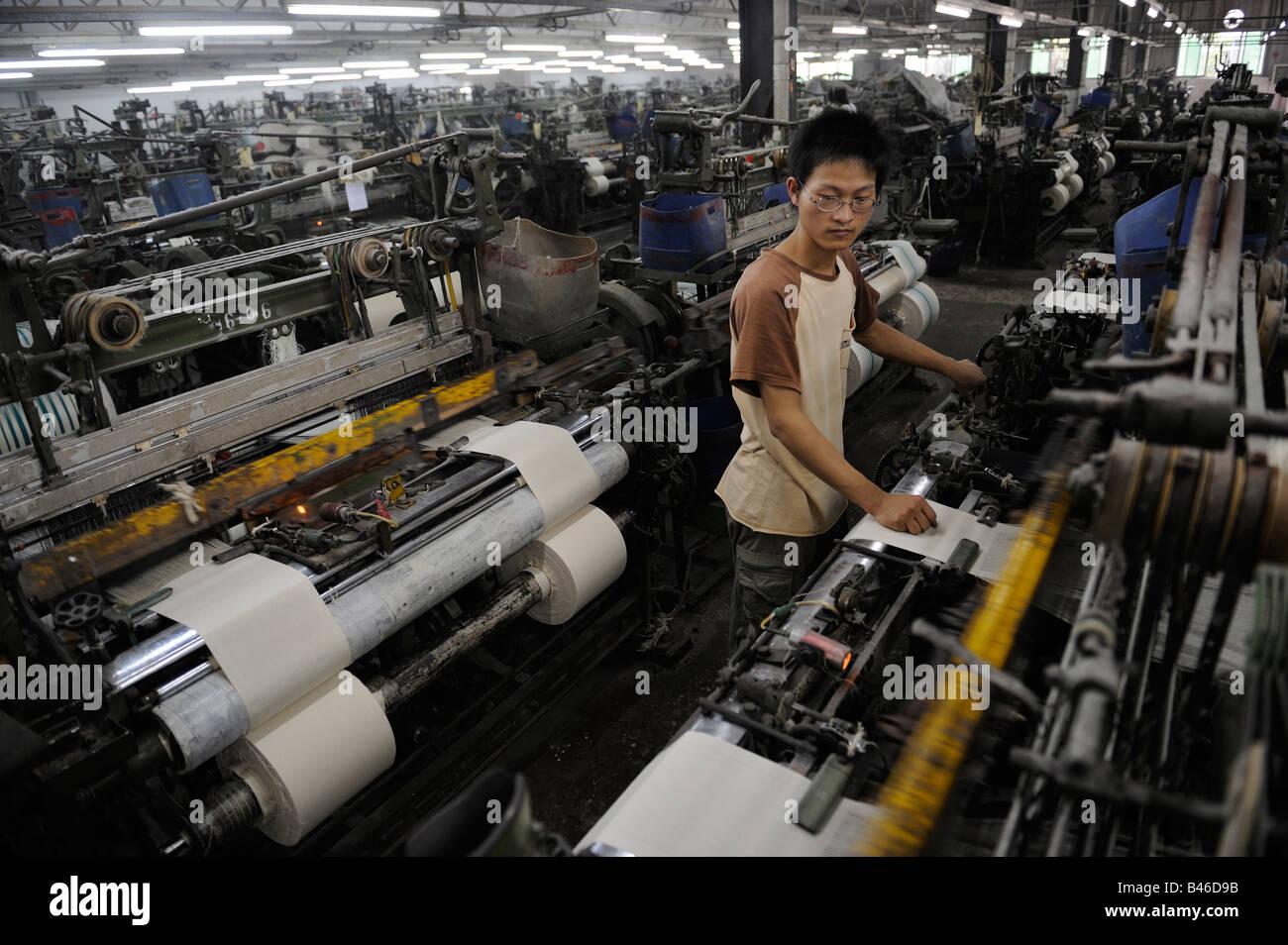 Jeune travailleur de l'utilisation de la machine dans une usine de textile à Foshan, Guangdong, Chine. 19-Sep-2008 Banque D'Images