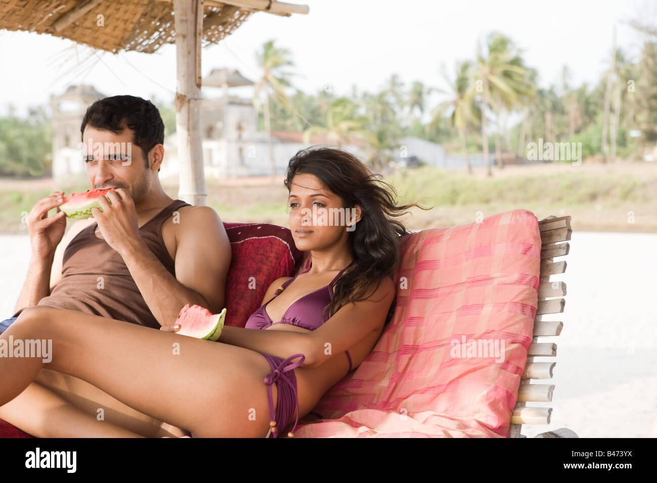 En couple avec chaises longues tranches de pastèque Photo Stock
