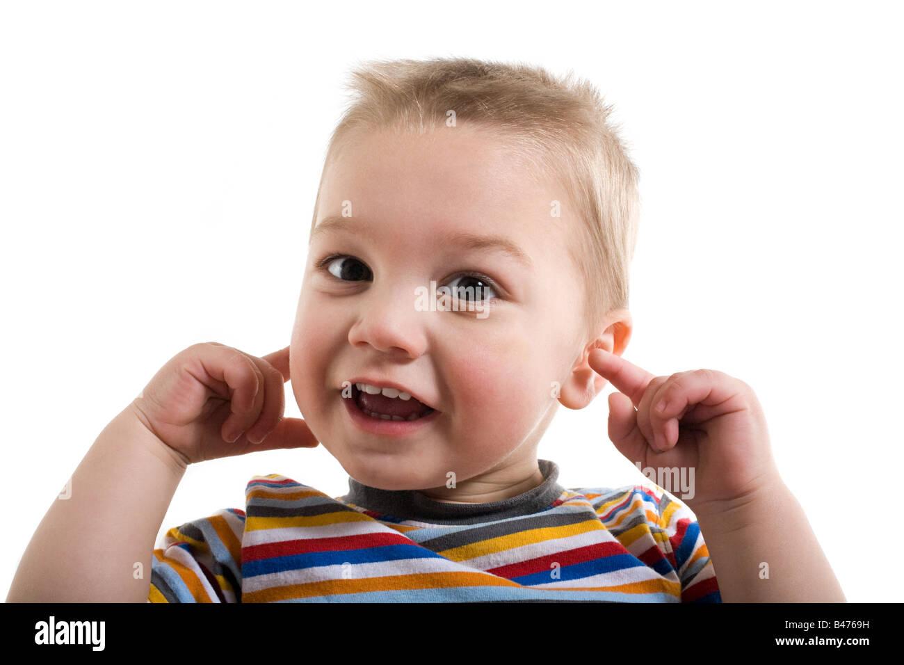 Un petit enfant avec ses doigts dans ses oreilles Photo Stock