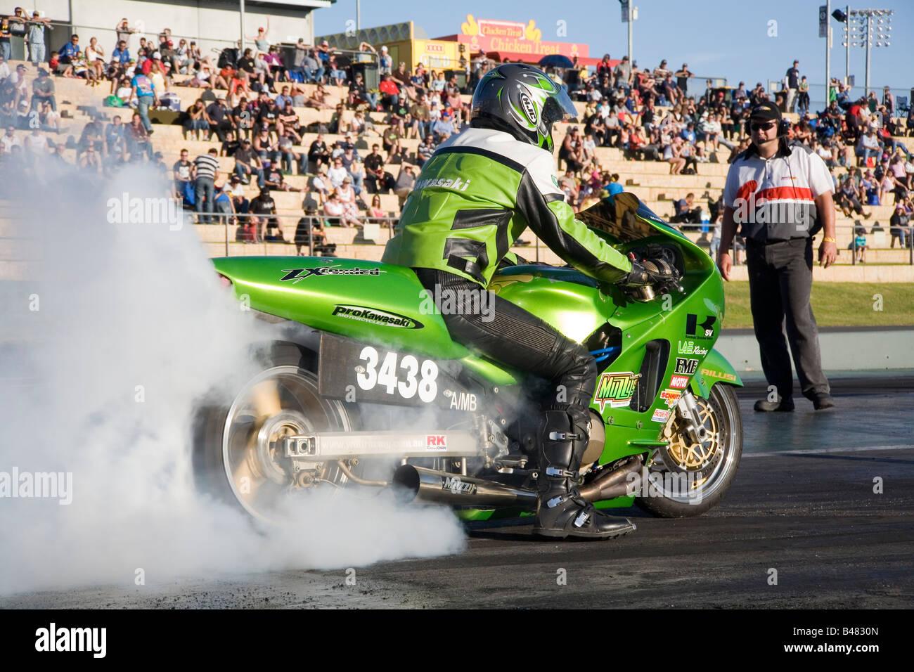 Une moto de course Kawasaki effectue un burnout pour réchauffer le pneu arrière avant la course sur le Photo Stock