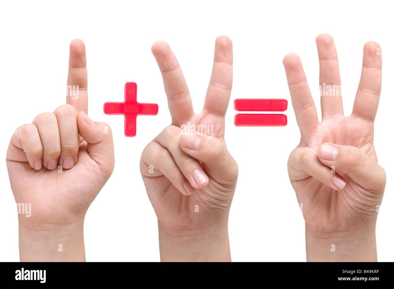 Les mains de l'enfant montrant l'un deux et trois doigts avec plus et le signe égal entre les deux Photo Stock