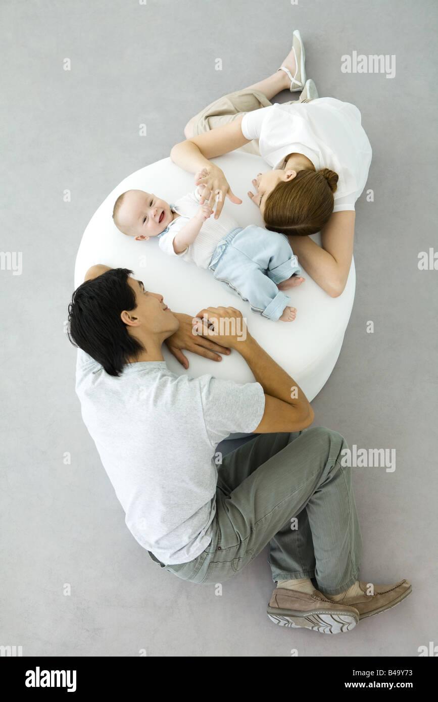 Les parents et le bébé se détendre sur un pouf, baby holding mother's hand, overhead view Banque D'Images