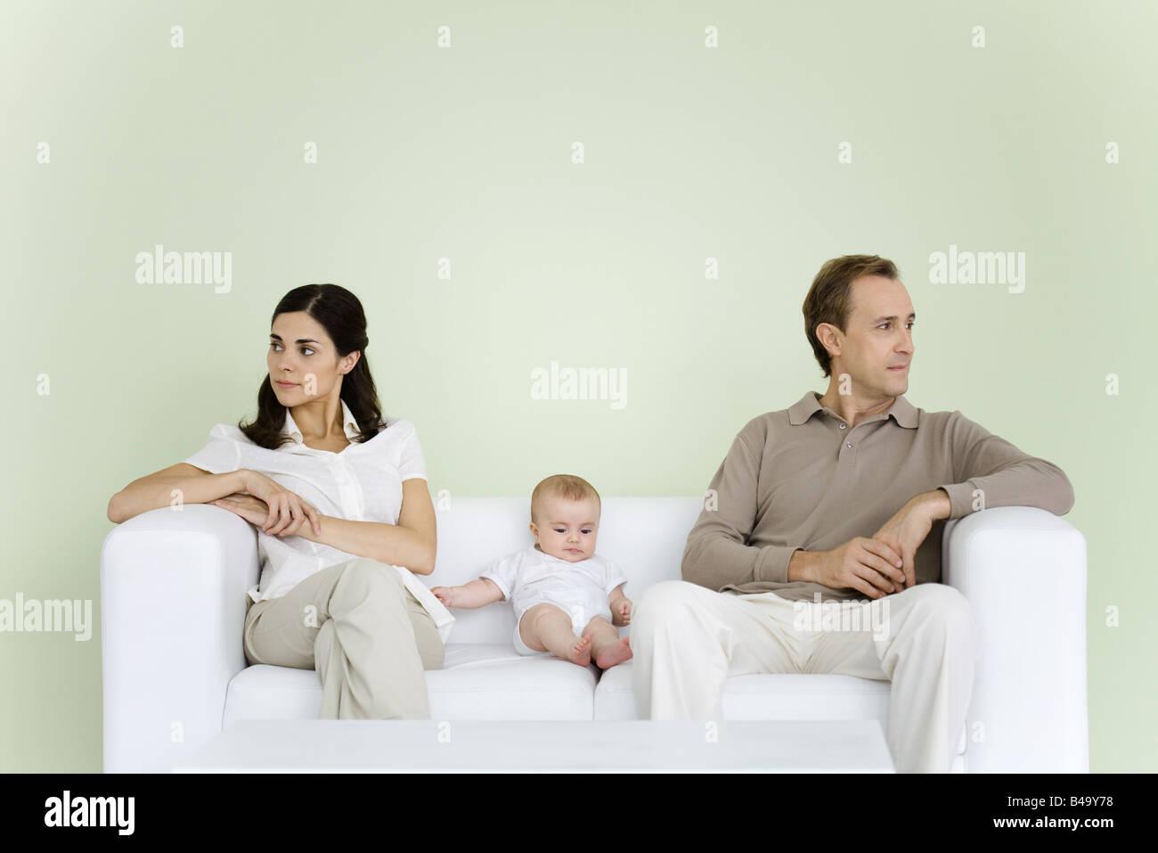 Couple sitting on couch avec bébé entre eux, tant à l'écart Banque D'Images