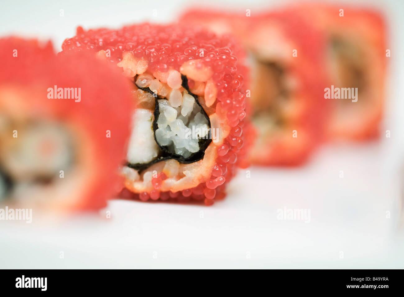 Portrait de maki sushi roulé en oeufs de poisson volant rouge, close-up Photo Stock