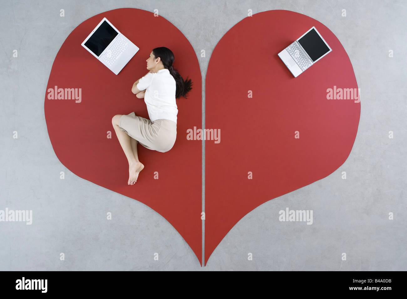 Femme couchée sur le sol avec un ordinateur portable sur un grand cœur brisé, abandonné derrière Photo Stock