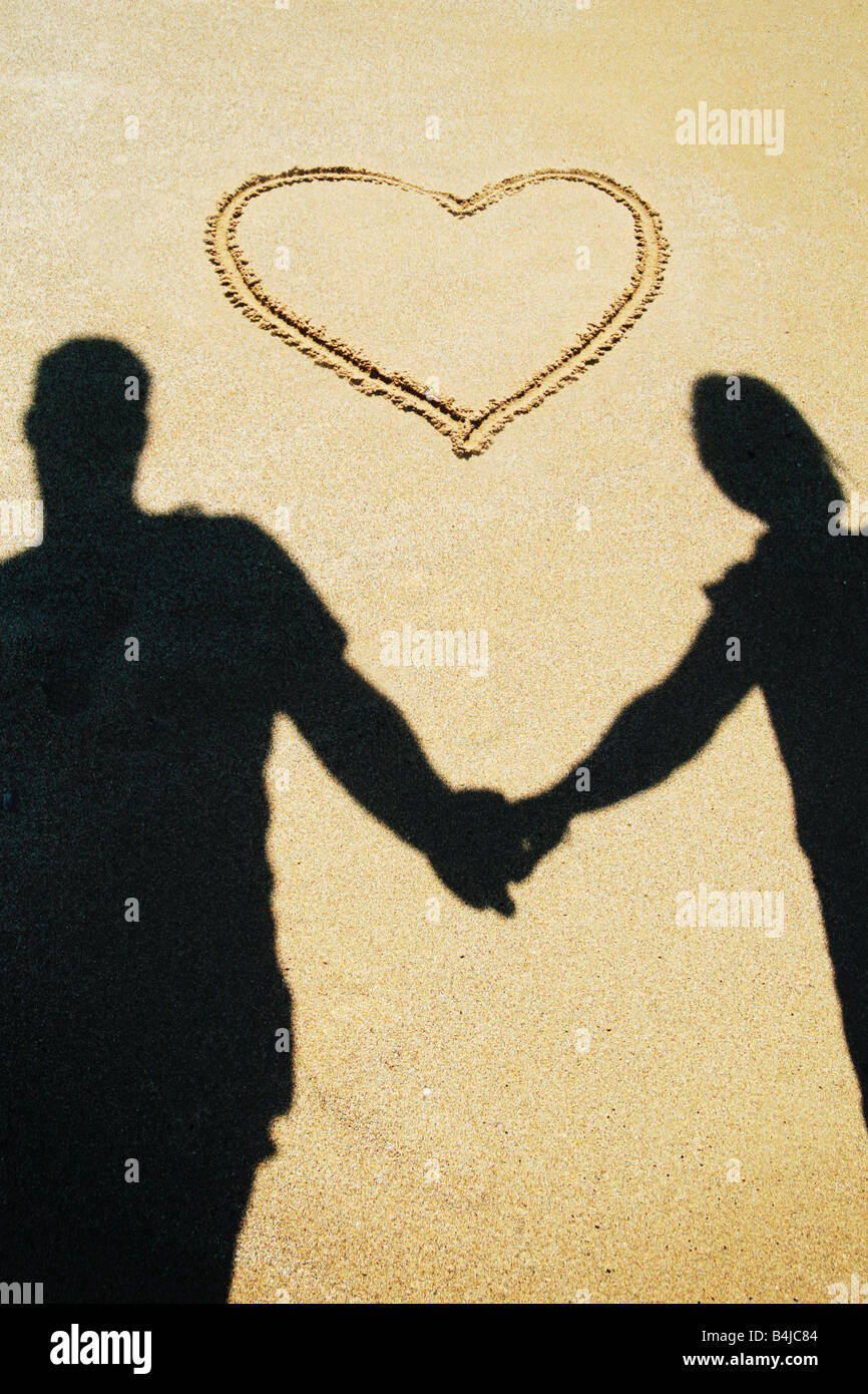 Le couple holding hands on beach Photo Stock