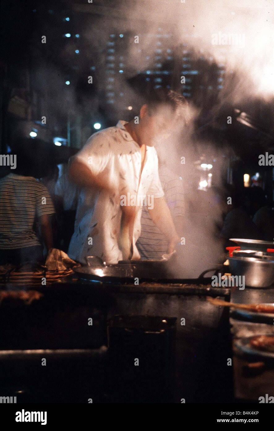 Hawker engloutie dans la vapeur comme il cuit les aliments dans le vieux quartier de Bugis Street Singapore circa Banque D'Images