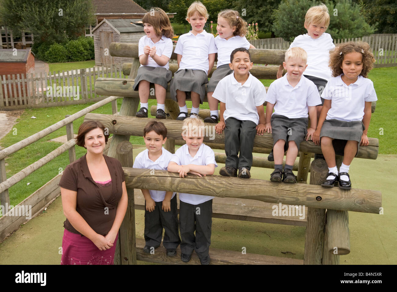 Les élèves assis à l'extérieur sur la structure en bois avec l'enseignant debout à côté d'eux Banque D'Images