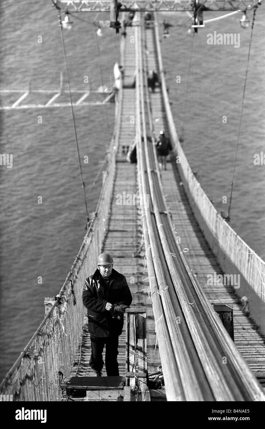 Le Forth Road Bridge est un pont suspendu à la différence du pont ferroviaire en porte-à-faux, Plusieurs propositions ont été rejetées avant la Mott Hay et Anderson design a été choisi c'est le premier pont suspendu de longue portée au Royaume-Uni d'autres ont bien sûr suivi le Severn Bridge et le Humber Bridge le Forth Road Bridge contient 39 000 tonnes d'acier le tours de 494 pieds au-dessus des fondations en béton et il a fallu un effectif de 300 à seulement trois ans et demi pour terminer la construction des ponts Workman Juin 1962 1960 Banque D'Images