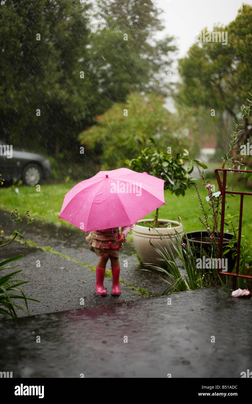 Fille dans la pluie avec un parapluie rose vieux de cinq ans Banque D'Images