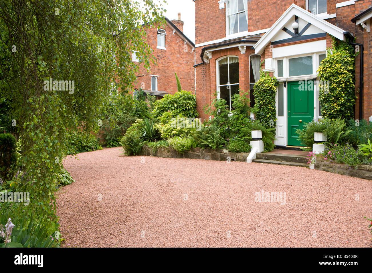 jardin de devant d 39 une grande maison individuelle avec all e en gravier rouge et les buissons de. Black Bedroom Furniture Sets. Home Design Ideas