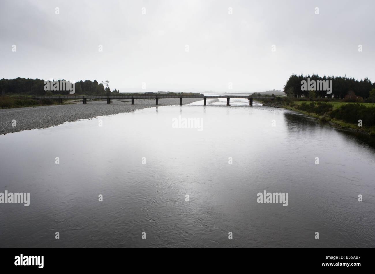 Pont sur la rivière Ahaura ciel gris reflète dans la rivière Côte ouest de l'île du Photo Stock