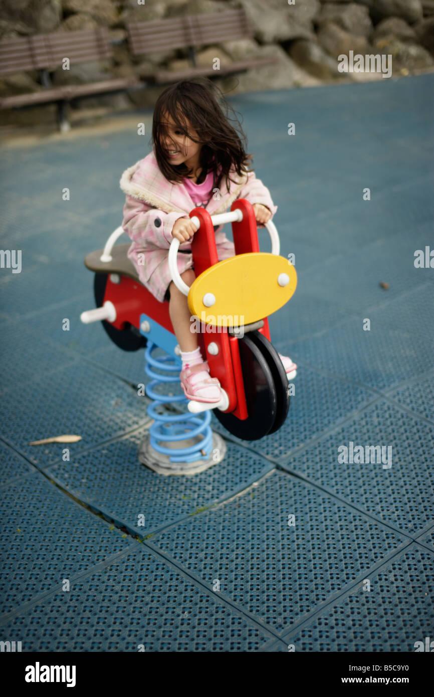 Jeune fille sur moto en jeu pour enfants Banque D'Images