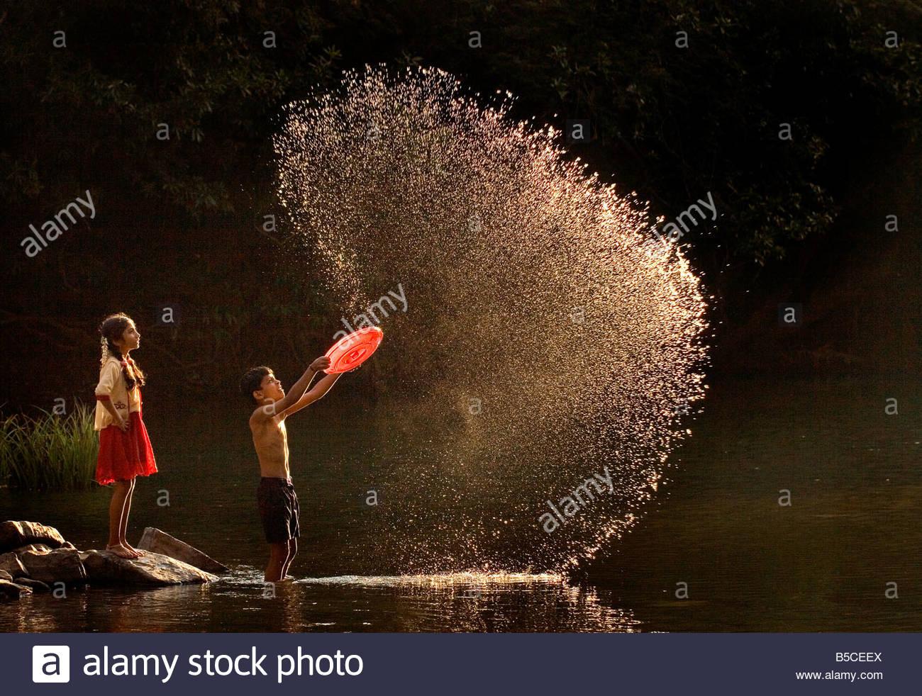 Enfants jouant PRÈS DE LA RIVIÈRE Photo Stock