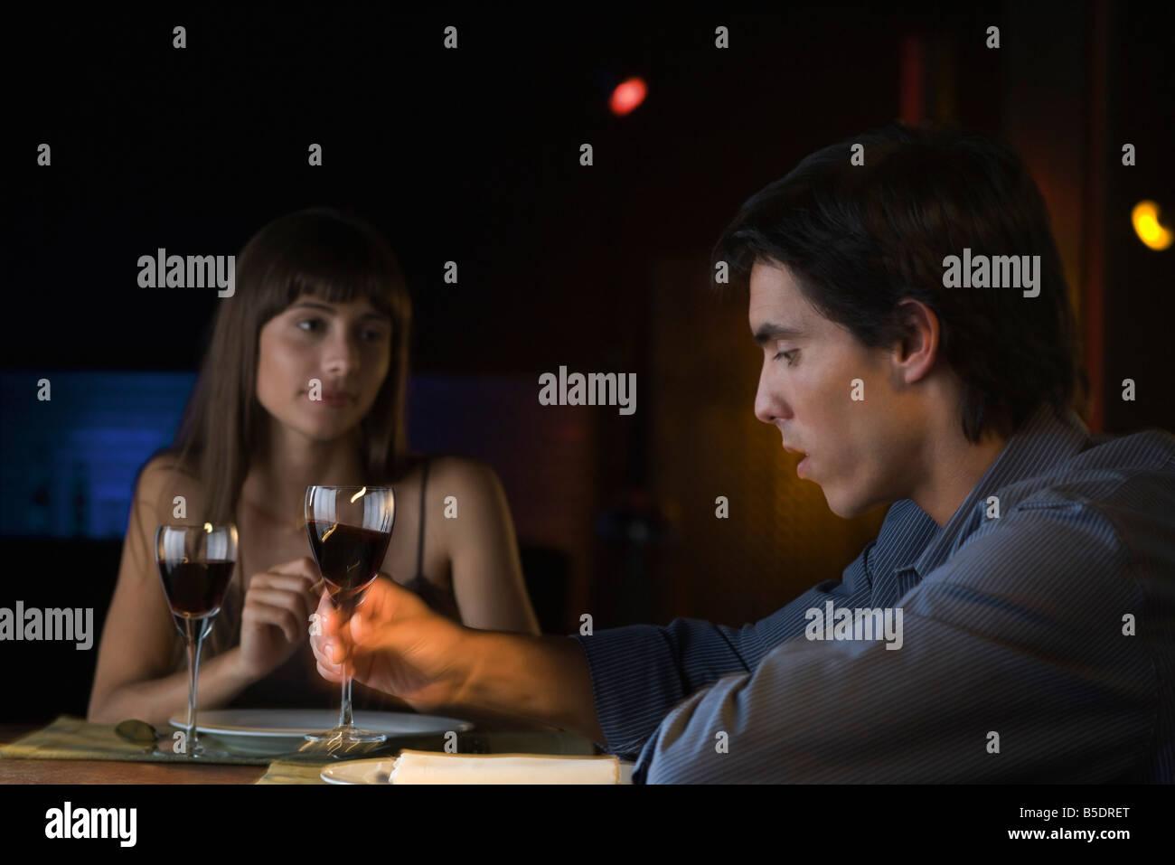 Couple having conversation sérieuse au cours d'un dîner au restaurant, l'homme prendre un verre de vin Banque D'Images