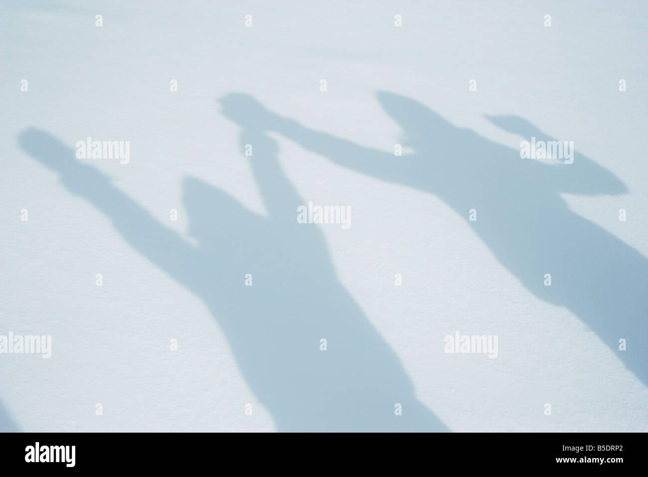 Ombre de personnes raising arms sur la neige Photo Stock