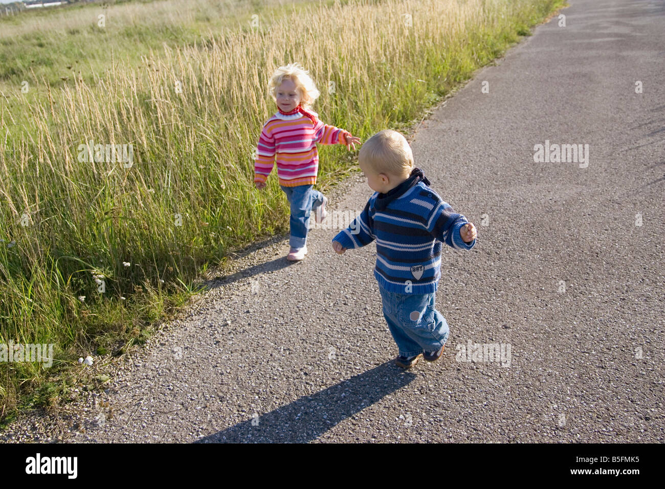 Little girl (2-3) and boy (1-2) à travers l'chemin Banque D'Images