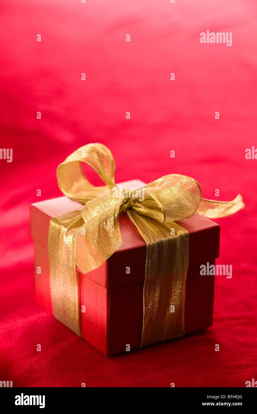 Boîte cadeau rouge avec un ruban d'or métallique Photo Stock