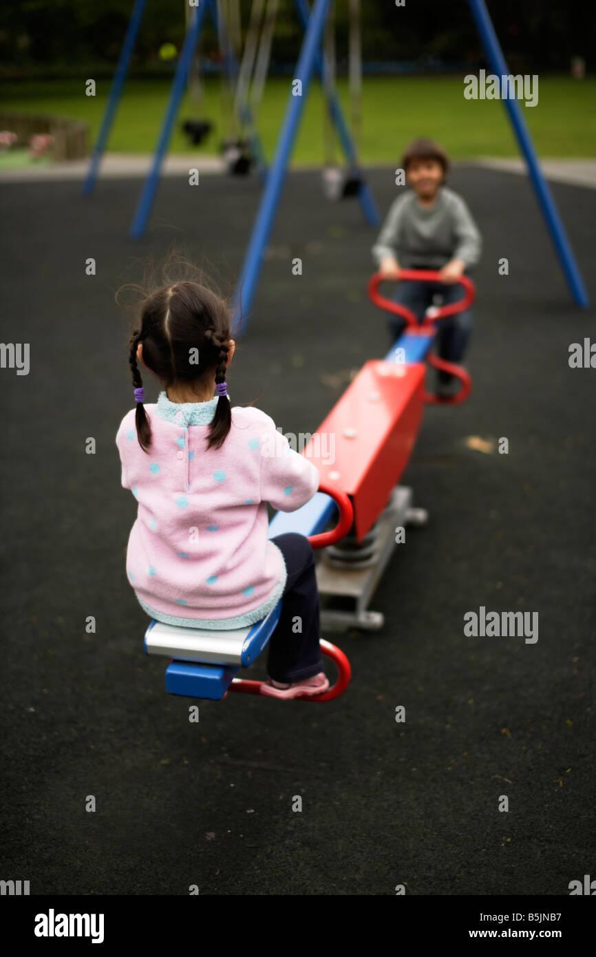 Six ans joue dans le parc avec balançoire sur cinq ans soeur Banque D'Images
